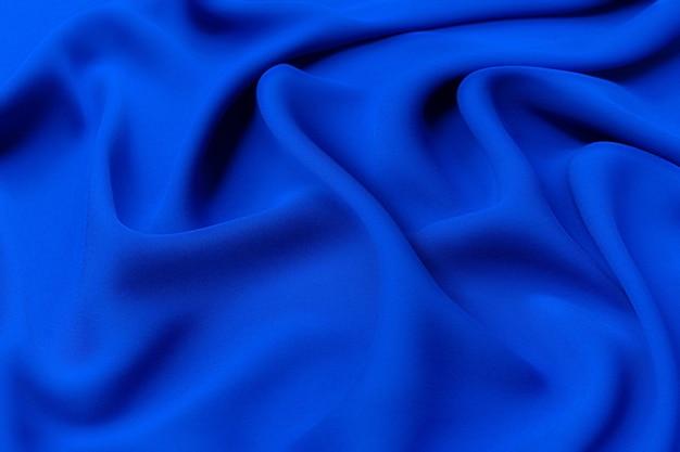 Glatte elegante blaue stoffseidenstruktur der blauen seide oder des satins als abstrakter hintergrund für design. luxuriöses muster