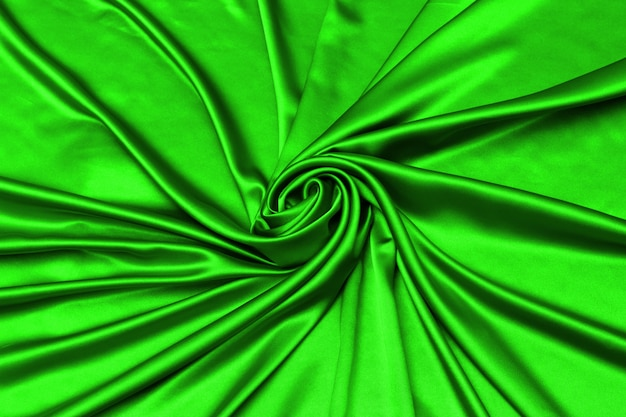 Glatte elegante grüne seide oder satin luxus stoff textur kann als abstrakter hintergrund verwendet werden.