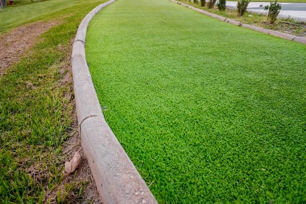 Glatte grasbahn für läufer, getrennt, in einem öffentlichen park.