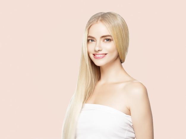 Glatte lange blonde haarfrau natürlich bilden gesunde haut. auf beige. Premium Fotos