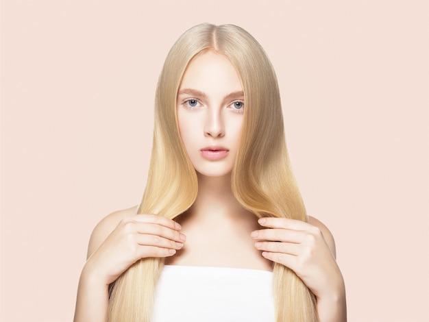 Glatte lange blonde haarfrau natürlich bilden gesunde haut. auf beige.