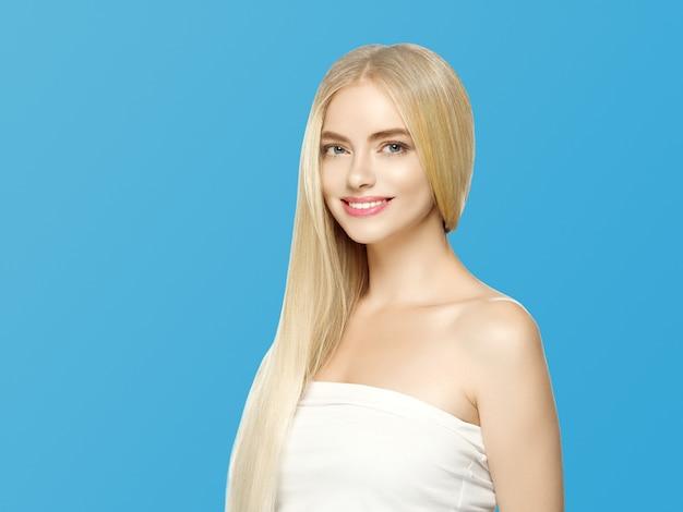 Glatte lange blonde haarfrau natürlich bilden gesunde haut. auf blau.