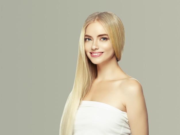 Glatte lange blonde haarfrau natürlich bilden gesunde haut. auf grau.