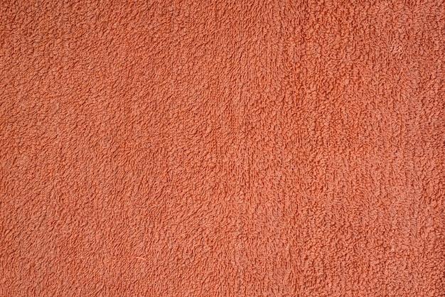 Glatte nahtlose textur eines frottee-handtuchs. korallenfarbe