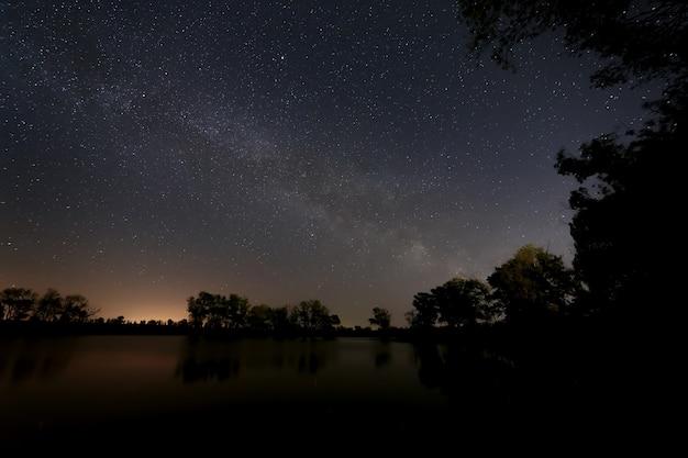 Glatte oberfläche des waldsees vor dem hintergrund des nachthimmels und der milchstraße.