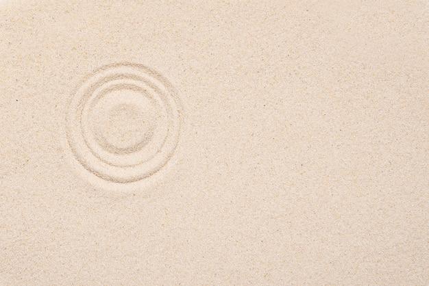 Glatte textur aus weißem sand mit rundem muster auf sandigem hintergrund.