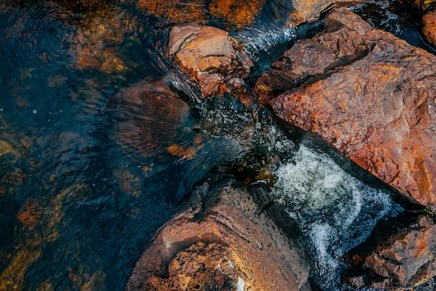 Glatte wassernahaufnahme der steine im frühjahr. sauberer wasserfluss zwischen roten und orangefarbenen steinen. bunter natürlicher gebirgsfrühlingsstrom mit copyspace. schöne beschaffenheit des nebenflusses mit nassen steinen.