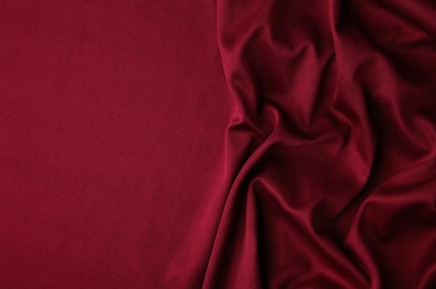 Glatter eleganter burgunderfarbener seiden- oder satin-luxus-stofftexturhintergrund.