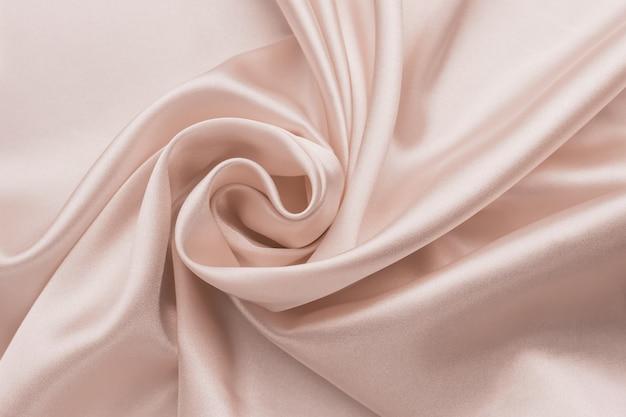 Glattes faltiges seidenbettlaken, stoffhintergrund. abstrakte zerknitterte satinbeschaffenheit.
