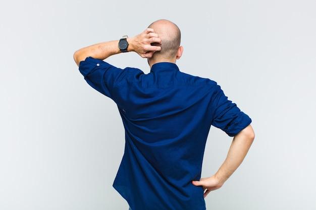 Glatze mann ahnungslos und verwirrt, eine lösung denkend, mit hand auf hüfte und andere auf kopf, rückansicht