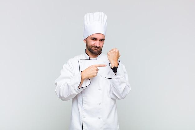 Glatze mann, der ungeduldig und wütend aussieht, auf die uhr zeigt und um pünktlichkeit bittet, will pünktlich sein