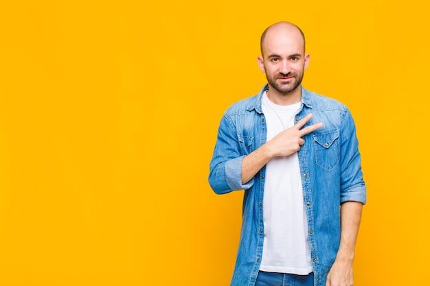Glatze mann fühlt sich glücklich, positiv und erfolgreich, mit der hand v form über der brust zu machen, sieg oder frieden zu zeigen