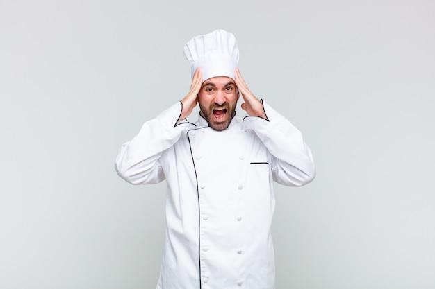 Glatze mann hebt die hände zum kopf, mit offenem mund, fühlt sich sehr glücklich, überrascht, aufgeregt und glücklich
