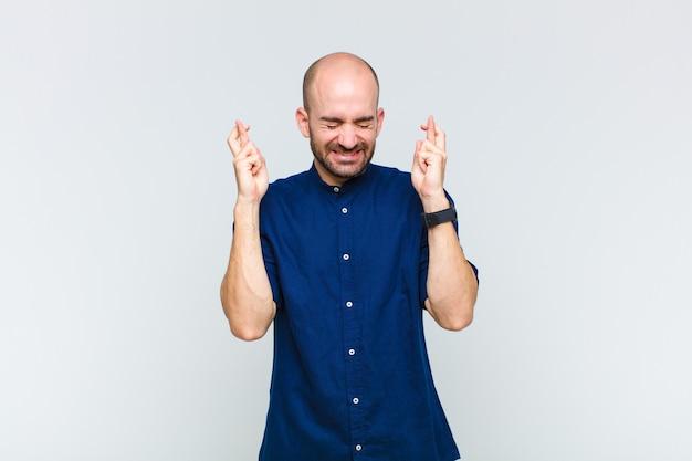 Glatze mann lächelt und kreuzt ängstlich beide finger, fühlt sich besorgt und wünscht oder hofft auf viel glück
