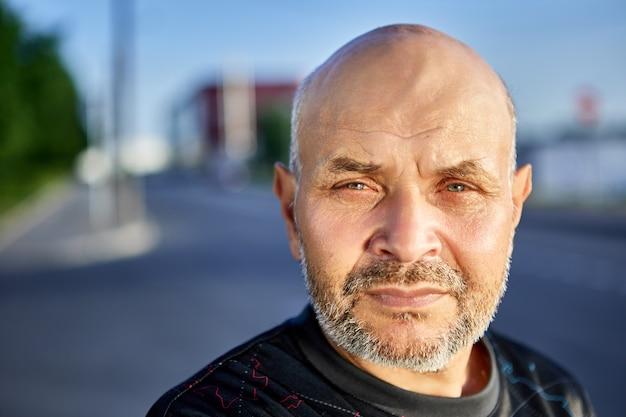 Glatzköpfiger älterer mann mit grauen stoppeln vor der stadtstraße