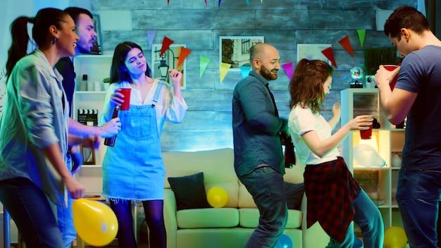 Glatzköpfiger attraktiver junger mann, der beim tanzen auf der party mit seinen freunden lächelt. wilde college-party mit neonlicht und discokugel