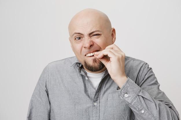 Glatzköpfiger bärtiger mann mittleren alters, der zähne berührt