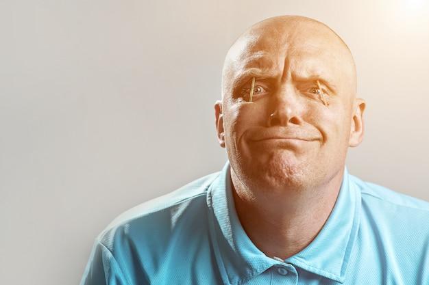 Glatzköpfiger brutaler mann in einem hellen t-shirt steckte streichhölzer in seine augen und schläft