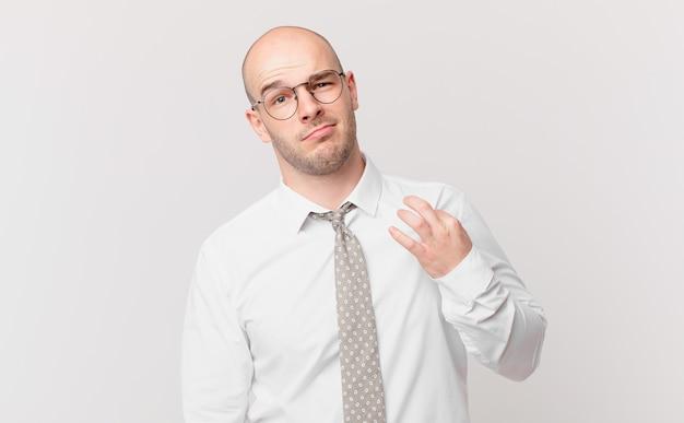 Glatzköpfiger geschäftsmann, der arrogant, erfolgreich, positiv und stolz aussieht und auf sich selbst zeigt