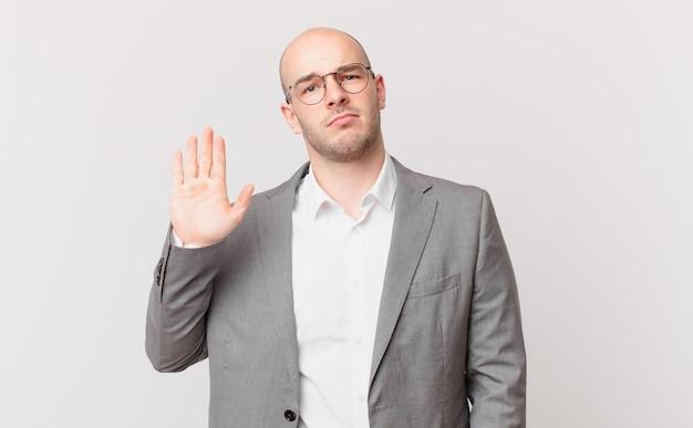 Glatzköpfiger geschäftsmann, der ernst, streng, unzufrieden und wütend aussieht und eine offene handfläche zeigt, die eine stopp-geste macht