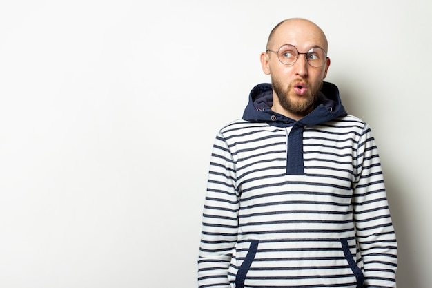 Glatzköpfiger junger mann mit bart in brille einer jacke mit kapuze schaut mit einem überraschten gesicht auf einem isolierten weiß weg. geste des schocks, überraschung