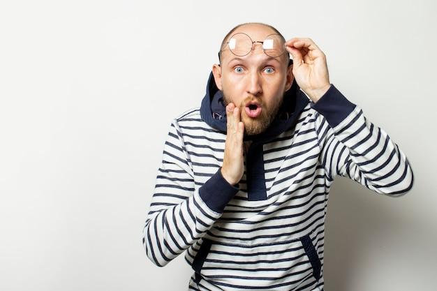 Glatzköpfiger junger mann mit bart, pullover mit kapuze auf der stirn mit einem überraschten gesicht auf isoliertem weiß. geste der überraschung, des schocks. speicherplatz kopieren