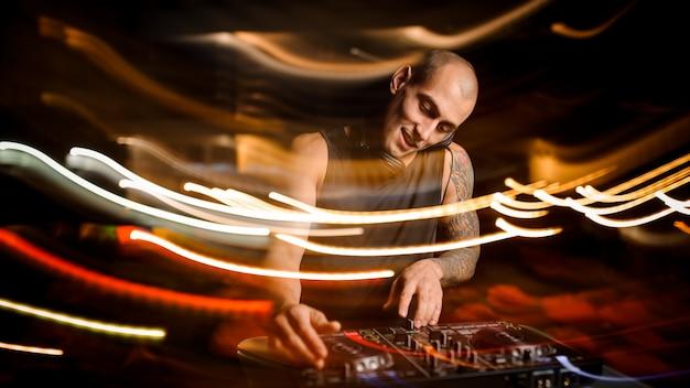 Glatzköpfiger lächelnder club dj mit kopfhörern mischt musik