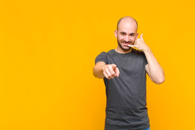 Glatzköpfiger mann, der fröhlich lächelt und zur kamera zeigt, während sie einen anruf tätigen, den sie später gestikulieren und am telefon sprechen