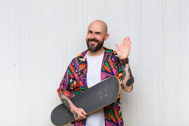 Glatzköpfiger mann, der glücklich und fröhlich lächelt, mit der hand winkt, sie begrüßt und begrüßt oder sich verabschiedet