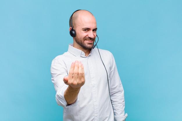 Glatzköpfiger mann, der sich glücklich, erfolgreich und selbstbewusst fühlt, sich einer herausforderung stellt und sagt, bring sie an! oder dich begrüßen
