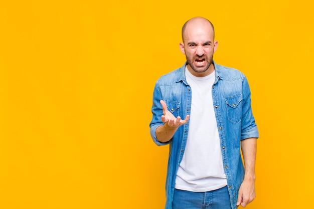 Glatzköpfiger mann, der wütend, genervt und frustriert aussieht und wtf schreit oder was mit dir los ist