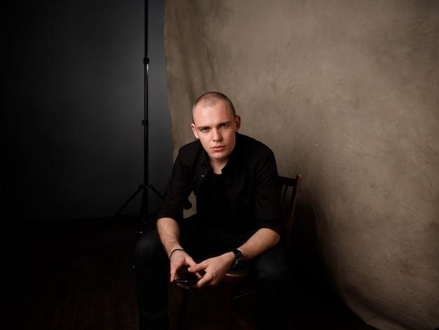Glatzköpfiger mann im schwarzen hemd sitzt auf studiostuhl. foto in hoher qualität
