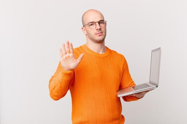 Glatzköpfiger mann mit computer sieht ernst, streng, unzufrieden und wütend aus und zeigt eine offene handfläche, die eine stopp-geste macht