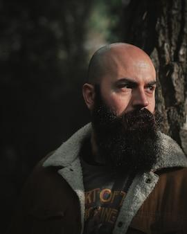 Glatzköpfiger mann mit einem dichten schwarzen schnurrbart im park, der zur sonne schaut