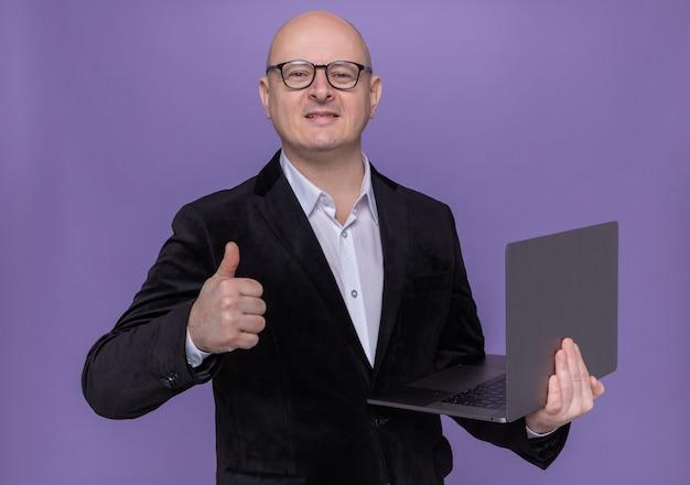 Glatzköpfiger mann mittleren alters im anzug, der eine brille hält, die laptop betrachtet, der vorne lächelt und fröhlich zeigt daumen zeigt, der über lila wand steht