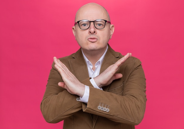 Glatzköpfiger mann mittleren alters im anzug, der eine brille trägt, die nach vorne schaut, mit ernstem gesicht, das stopp-geste kreuzt, die hände über rosa wand steht