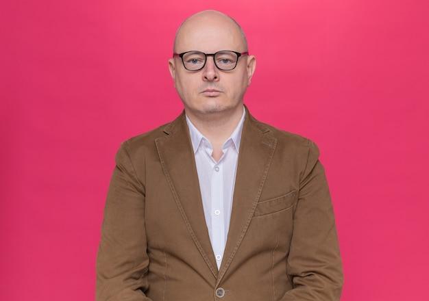 Glatzköpfiger mann mittleren alters im anzug, der eine brille trägt, die vorne mit ernstem selbstbewusstem ausdruck über rosa wand steht