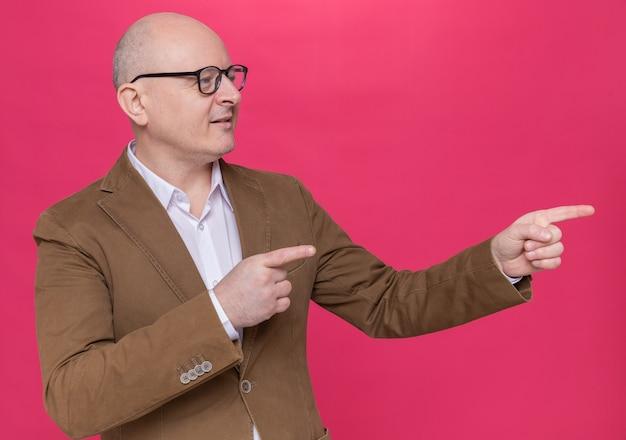 Glatzköpfiger mann mittleren alters im anzug, der eine brille trägt, die zur seite schaut und selbstbewusst mit zeigefingern zur seite zeigt, die über rosa wand steht