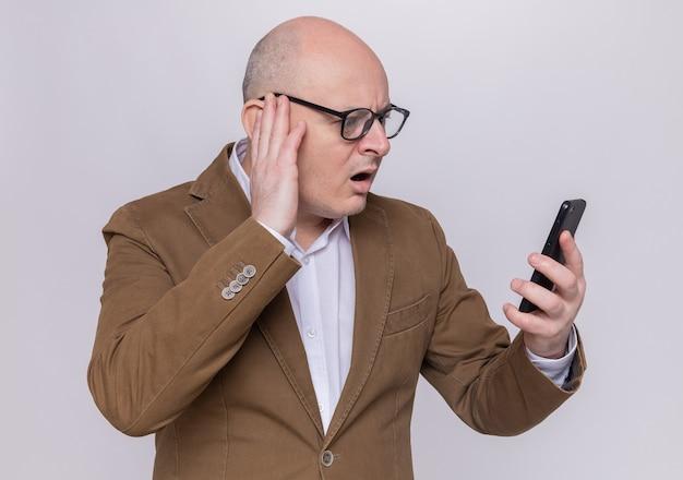 Glatzköpfiger mann mittleren alters im anzug, der eine brille trägt und verwirrt auf sein handy schaut