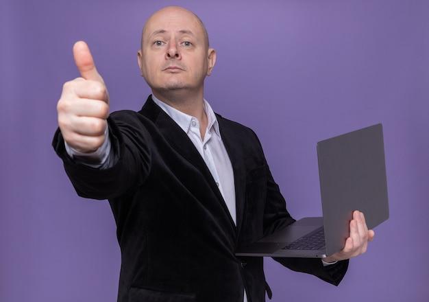 Glatzköpfiger mann mittleren alters im anzug, der laptop hält, der vorne mit lächeln auf intelligentem gesicht zeigt daumen zeigt, der über lila wand steht