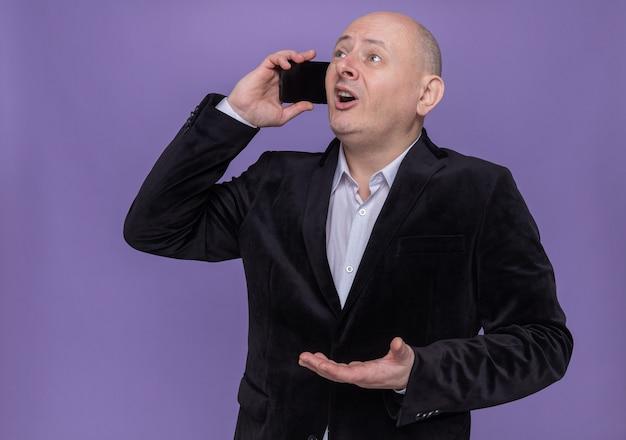 Glatzköpfiger mann mittleren alters im anzug, der überrascht und glücklich aussieht, während er auf handy spricht, das über lila wand steht