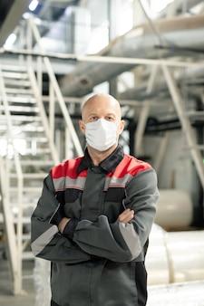 Glatzköpfiger reifer arbeiter in uniform und schutzmaske, der die arme an der brust verschränkt, während er gegen die treppe in der polymerverarbeitungsfabrik steht