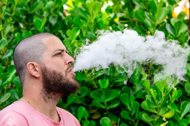 Glatzköpfiger und bärtiger mann raucht