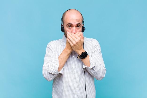 Glatzkopf bedeckt den mund mit den händen mit einem schockierten, überraschten ausdruck