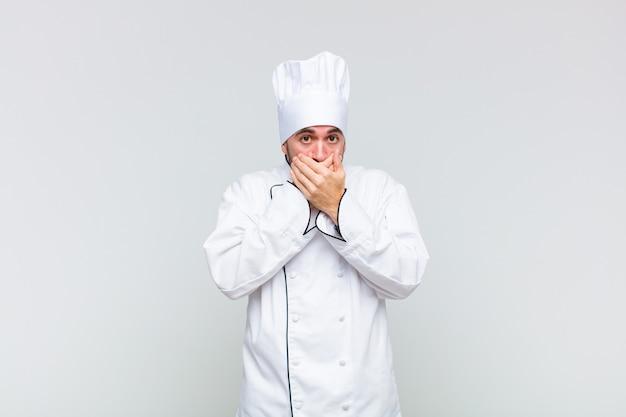 Glatzkopf bedeckt den mund mit händen mit einem schockierten, überraschten ausdruck, hält ein geheimnis oder sagt oops