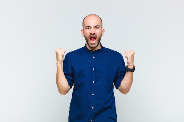 Glatzkopf, der aggressiv mit einem wütenden ausdruck oder mit geballten fäusten schreit, um erfolg zu feiern