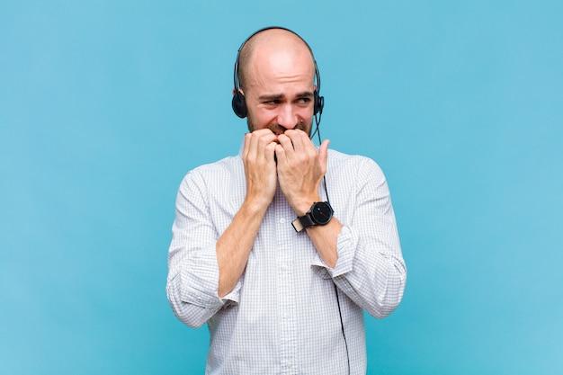 Glatzkopf, der besorgt, ängstlich, gestresst und ängstlich aussieht, fingernägel beißt und zum seitlichen kopierraum schaut