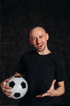 Glatzkopf, der fußball zeigt