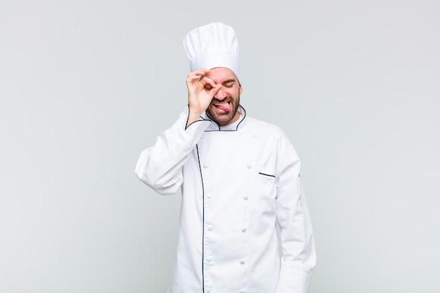 Glatzkopf, der glücklich mit lustigem gesicht lächelt, scherzt und durch guckloch schaut, geheimnisse ausspioniert