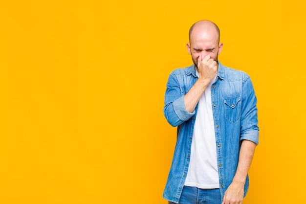 Glatzkopf, der sich angewidert fühlt und die nase hält, um einen üblen und unangenehmen gestank zu vermeiden